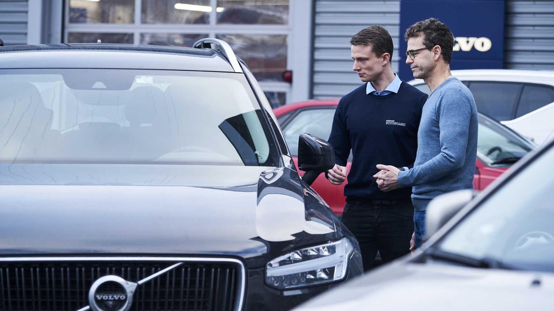Sælger snakker med kunde foran bil
